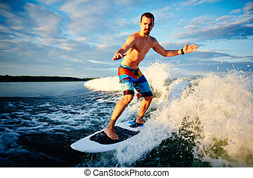 Summer sport - Active young man spending leisure surfing on...