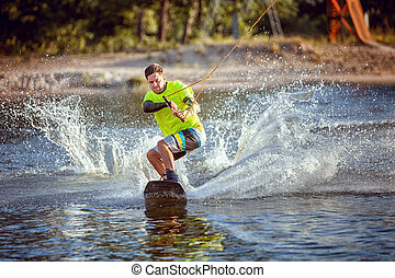 Summer sport wakeboarding. The sportsman slides on the...