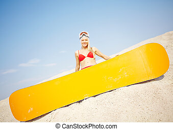 Summer sport - Yellow snowboard on sand with happy girl on...