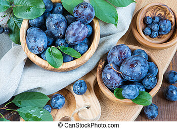 Summer still life - Blue ripe plums with green leaves in...
