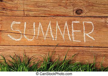 Summer written in chalk on a wooden fence.