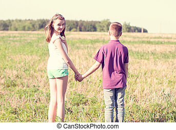 Summer sunny day park stands  boy with  girl holding hands enjoy nature, Meadow, fun small little family relationships,  idea concept  happiness lifestyle