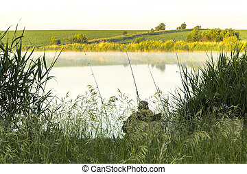 Summer sunny landscape. Morning, dawn on the lake. A fisherman sits on the shore with a fishing rod. Saratov Region, Russia.
