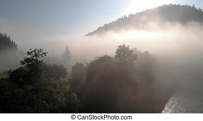 Summer sunrise in the foggy mountain village. Early morning on the river in summer. Beautiful countryside landscape.