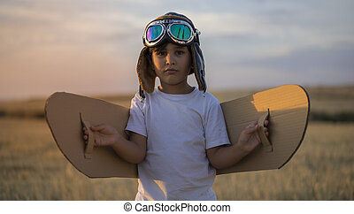 Summer sunset, Boy playing to be airplane pilot, funny guy with aviator cap and glasses, carries in his hand a plane made of paper