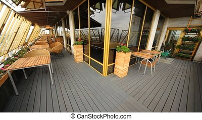 Summer tables of restaurant stands on terrace under build...