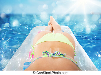 Summer tanning on airbed - Girl tans on airbed at the sea