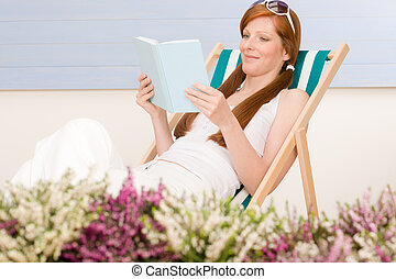Summer terrace red hair woman relax in deckchair garden