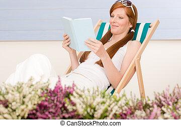 Summer terrace red hair woman relax in deckchair garden