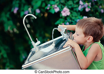 little boy reaching for the tap water in the street to get a drink of water