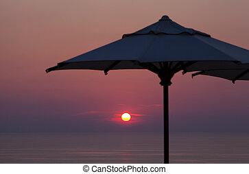 Summer time: beautiful cloudy dawn with parasol at background