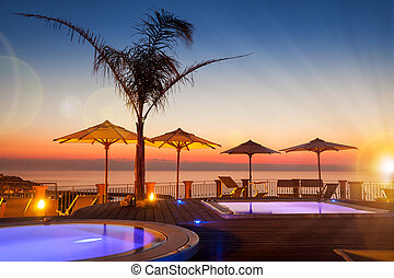 Summer time: beautiful view of red dawn at pool area with palm and parasols at