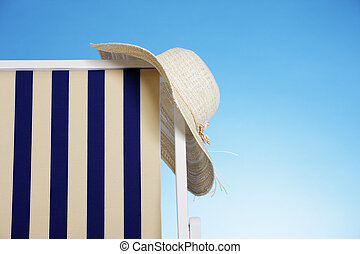 Summer time - straw hat in a beach chair