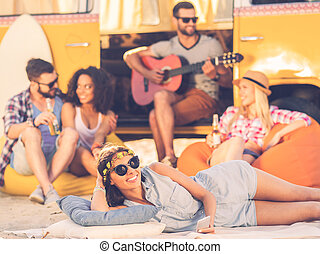 Summer time with friends. Cheerful young woman smiling at camera while lying near retro minivan with friends in the background