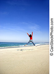 Summer time - Young woman jumping on the beach and having...