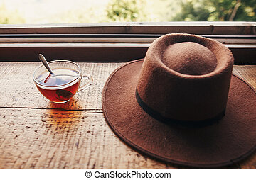 summer travel and wanderlust. stylish hipster hat and tea in glass with spoon on wooden table at window light with view on mountains and sky. delicious hot drink on mountain top.