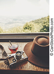 summer travel and wanderlust. stylish hipster hat, photo camera and tea in glass with spoon on wooden table at window light with view on mountains and sky. delicious hot drink on top