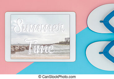 Summer Travel poster on tablet screen with 2 beach sandals