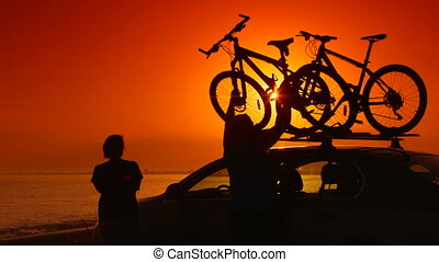 Summer travelers near his car with mounted bikes on beach vacation