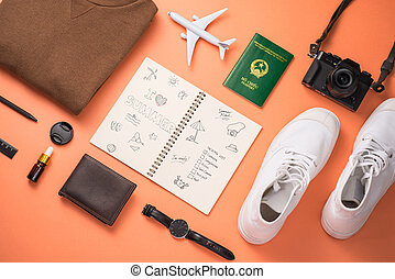 Summer traveling concept. Vacation accessories on orange background.