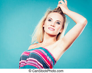 Blonde woman wearing colorful striped strapless shirt -...