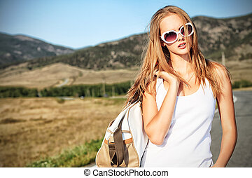 summer trip - Beautiful young woman posing on a road over ...