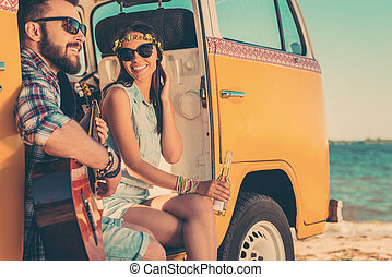 Summer tunes. Happy young couple enjoying time together while sitting in their retro minivan with sea in the background