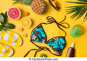 Beach accessories on yellow background