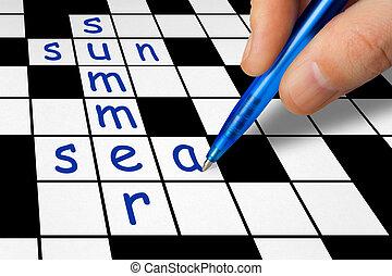 Summer vacation concept - Hand filling in crossword - summer...
