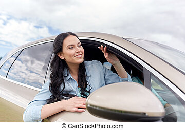 happy young woman driving in car