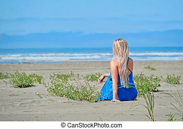 Summer vacation on beach. Woman on beach looking at the sea.