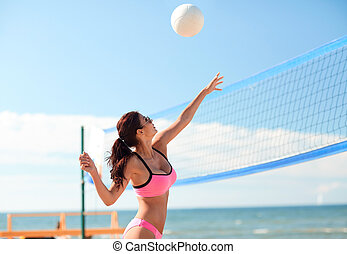 young woman with ball playing volleyball on beach
