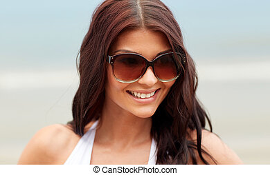 smiling young woman with sunglasses on beach