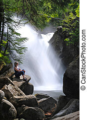 Summer vacation travel in British Columbia, Canada. Woman on rock by beautiful watherfalls. Vancouver. BC. Canada.