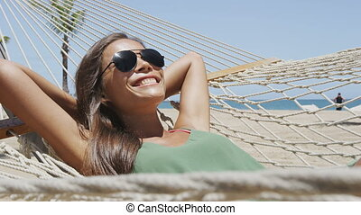 Summer vacation woman lying down on beach hammock putting on sunglasses, relaxing sunbathing under the tropical sun resting on outdoor patio furniture swing bed at Caribbean resort.