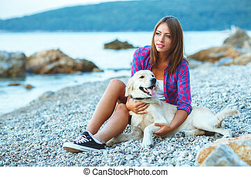 Summer vacation, woman with a dog on a walk on the beach