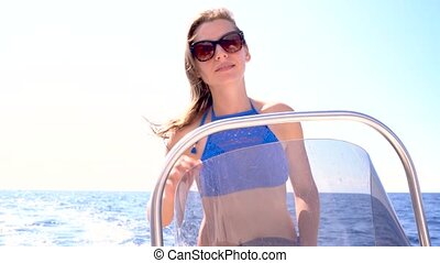 Summer vacation - young girl driving a motor boat on the sea