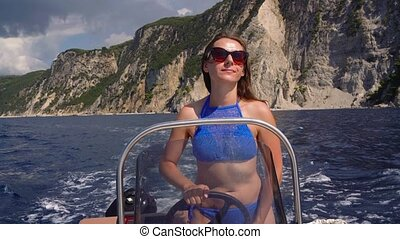 Summer vacation - young girl driving a motor boat on the...