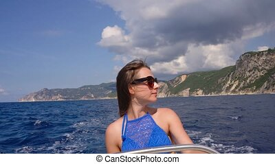 Summer vacation - young girl driving a motor boat on the sea...