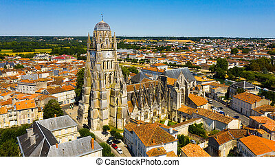 Picturesque summer view of historic areas of Saintes located on Charente river looking out over cathedral bell tower in Flamboyant Gothic style, Charente-Maritime, France..