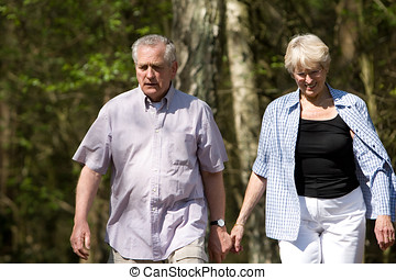 Summer walk - Senior couple out on a summer day strolling ...