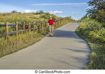 Senior man is walking on the Poudre River Trail in northern Colorado near Windsor. It is a paved bike trail extending more than 20 miles between Timnath and Greeley.