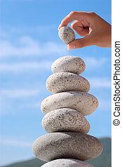 equilibrium - Summer. Wild beach. Someone's hand constructs...