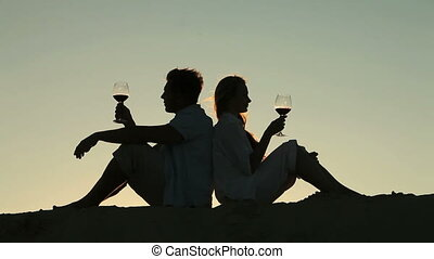 Peaceful lovers drinking red wine at sunset