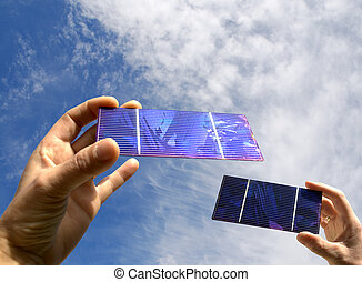 Summer with solar - two hands with solar cell against a...