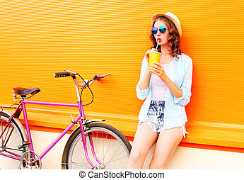 Summer woman drinks fruit juice from cup with retro bicycle on a colorful orange background