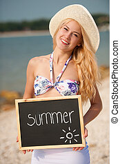 summer - woman with blackboard on the beach