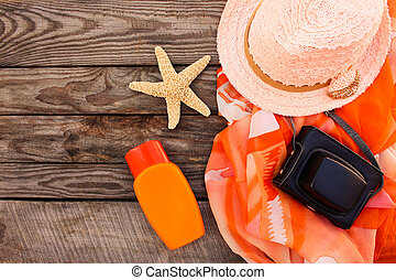 Summer women's beach accessories for your sea holiday on the old wooden background. Toned image.