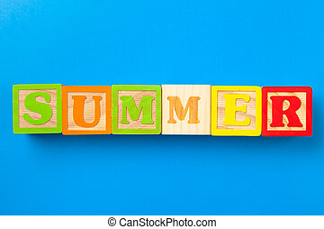 Summer. Wooden colorful alphabet blocks on blue background, flat lay, top view.