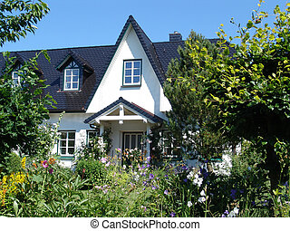 northern german house, surrounded by plants and flowers